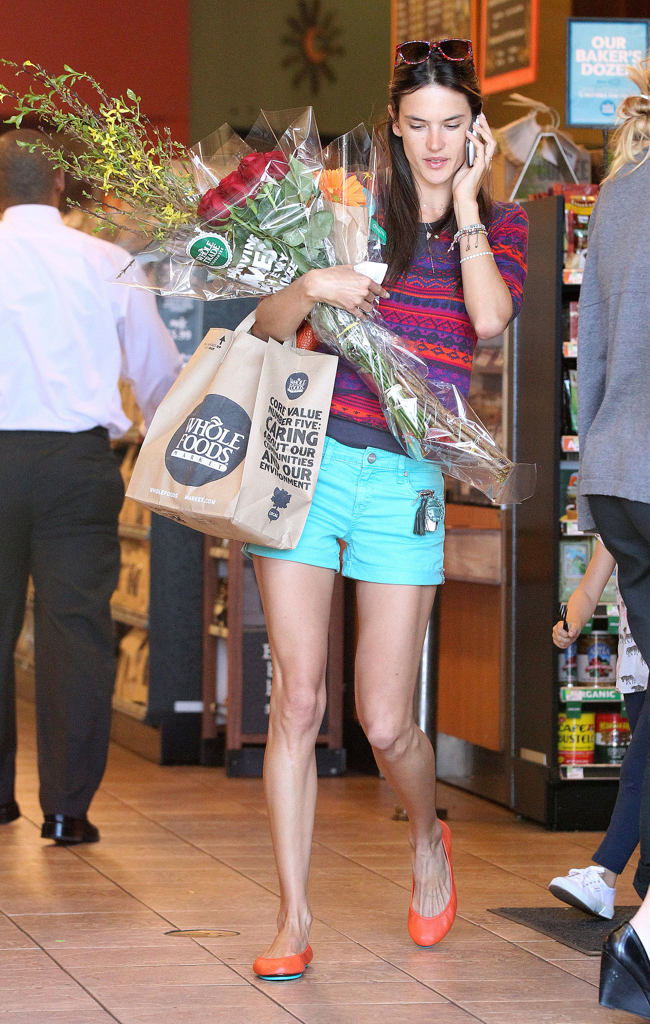 Alessandra stood out as she shopped for groceries in a colorful ensemble, which included turquoise denim shorts by Sanctuary, a printed sweater, and orange ballet flats.