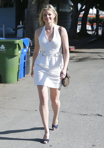 Amy Smart enjoyed a warm day out in LA in a plunging white halter dress, navy peep-toes, and a brown leather shoulder bag. We love the gold hardware on the waist of the dress.