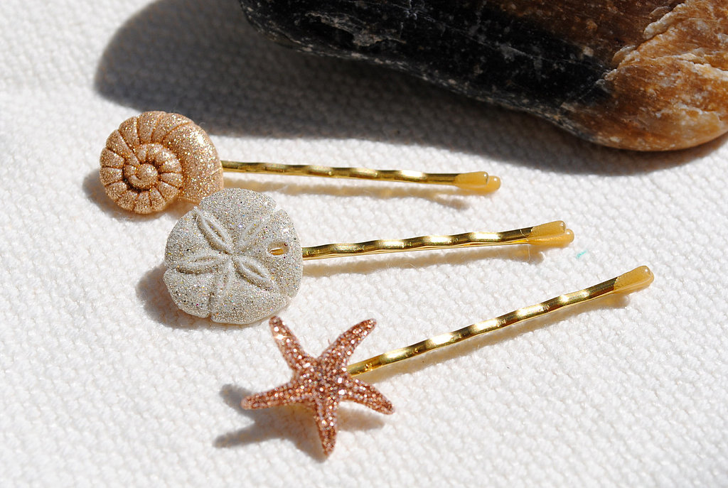 Go for a subtle beach theme with these glittering seashell bobby pins ($7).
