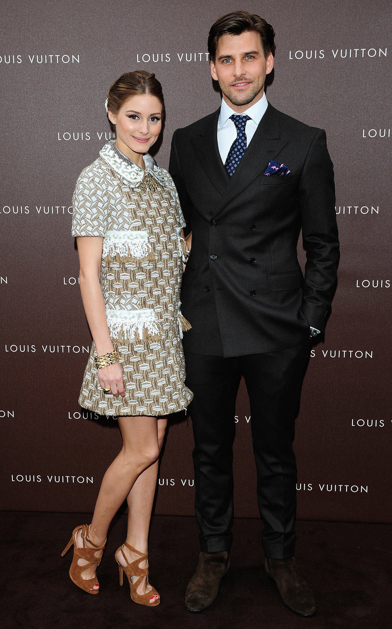 At the Louis Vuitton Maison opening in Munich, Olivia Palermo — pictured with boyfriend Johannes Huebl — mixed high with low in a metallic collared Louis Vuitton Resort '13 dress and tan suede Zara sandals.