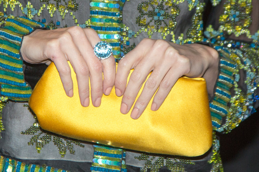 Paz Vega wore a circular blue ring and carried a satin yellow clutch.