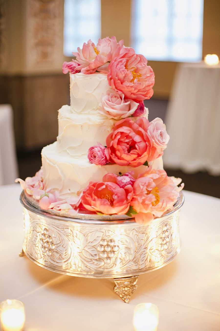 One easy way to make your cake feel supergirlie and sweet (aside from cascading flowers, of course)? A silver or gold cake stand that's just as detailed.  Photo by Annabella Charles Photography via Style Me Pretty