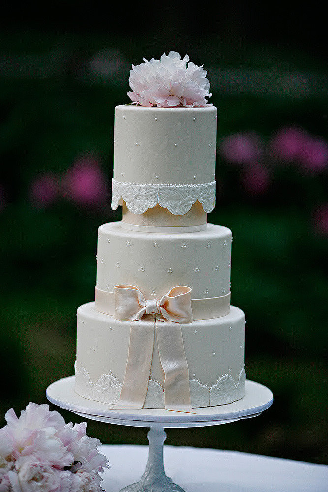 It's got pearls, it's got a bow, it's got a lace-like pattern, and it's got flowers — yet this cake still manages to be sweet and romantic in the simplest way.  Photo by Marie Labbancz Photography via Style Me Pretty