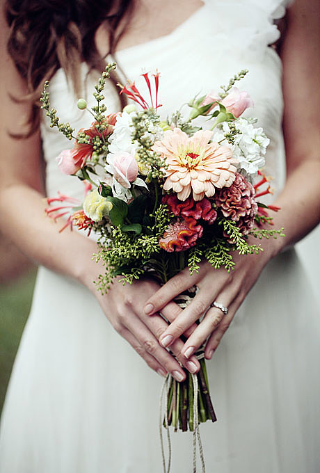"""A Wildflower Bouquet in Peaches and Creams """"These flowers (cockscombs, zinnias, hyacinth beans, old-fashioned garden roses, honeysuckle, pieris, vitex, and phlox) were picked the morning of the wedding to preserve their fresh fragrance and form,"""" explains Hannah Warfield of North Carolina-based Flora Verdi, a supporter of the local-seasonal-and-sustainable phenomenon. """"This is a late-Summer arrangement, echoing the warm tones of the season: peach, orange, cream, and rust-kissed greens. It's ideal for a wedding taking place in a romantic garden with an antiqued look,"""" says Warfield. Browse more romantic wedding flower ideas. Related: Beautiful Wedding Cakes For Every Season Source: Eleise Theuer Photography"""