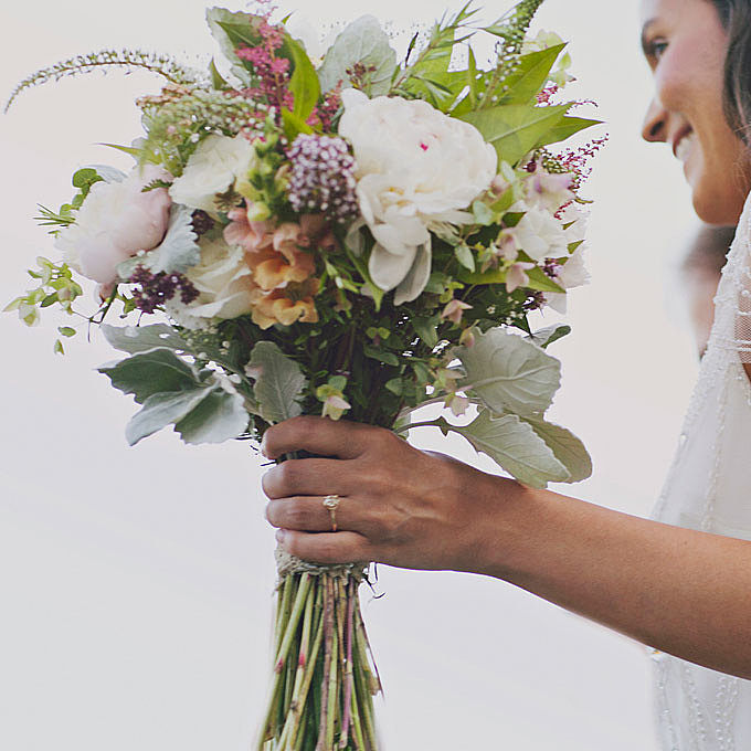 """A Loose """"Green"""" Arrangement for an Outdoor Wedding """"Our bride asked for wild, rustic, bohemian, earthy, and not perfect or stuffy, and I hope we nailed it,"""" says Ellen Frost, owner of Maryland-based Local Color Flowers. Frost specializes in locally grown cut flowers sourced from within 100 miles of Baltimore. """"Sourcing locally is a great alternative to using flowers that are shipped from places like Colombia, Ecuador, and Kenya,"""" explains Frost. """"Right now, 80 percent of the flowers sold in the U.S. come from thousands of miles away, outside the country."""" To achieve this ecoconscious, fresh-from-the-garden look, Frost used peonies, snapdragons, astilbes, yarrow, and lisianthus and paired them with dusty millers, oregano, rosemary, and mountain mint. Browse more rustic wedding flower ideas. Related: Honeymoon Finder Quiz Source: Our Labor of Love"""