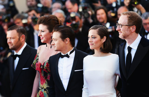 Jeremy Renner and Marion Cotillard stopped for pictures with James Gray before the premiere for The Immigrant on Friday.