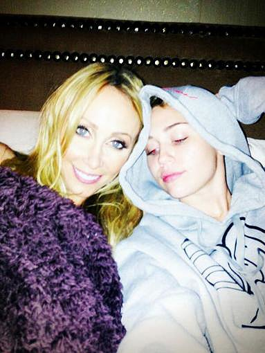 "Miley Cyrus snapped a photo while hanging in bed with her mum, Tish, with the caption ""Nothing a little mommy time can't fix."" Source: Twitter user MileyCyrus"