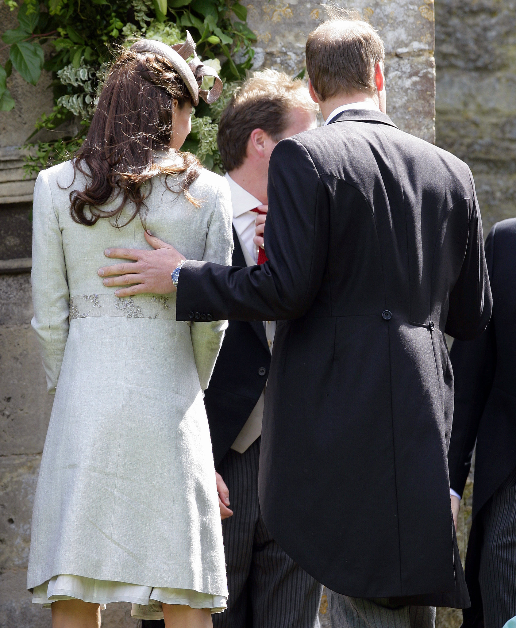 William rested his hand on Kate's back at a wedding in June of 2012.