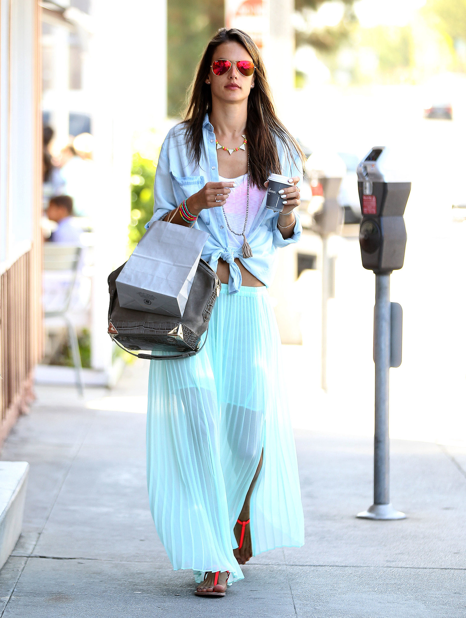 Alessandra Ambrosio colored the streets in a minty pleated maxi skirt, a chambray Sam & Levi shirt, and mirrored Ray-Ban aviator sunglasses.