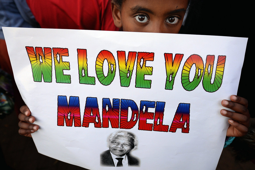 Near the hospital, a young child held up a sign of support for Mandela.