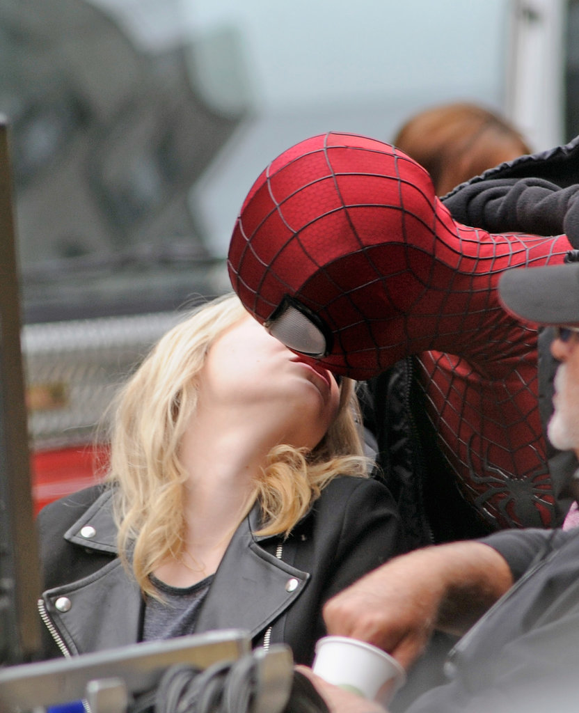 Emma Stone snuck a kiss with her masked boyfriend, Andrew Garfield, off camera on their The Amazing Spider-Man 2 set in NYC.
