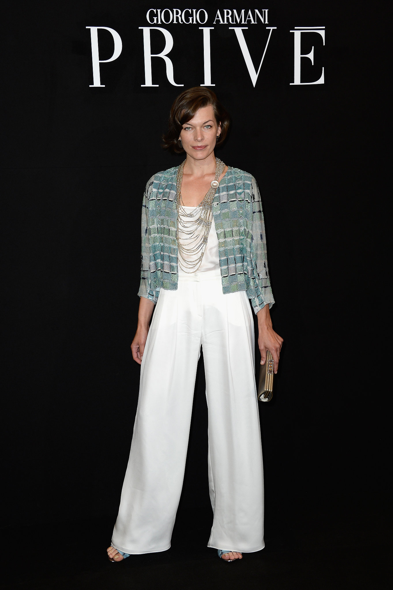 Milla Jovovich added dramatic flair to her all-white outfit at the Armani Privé show with a blue jacket and multistrand necklace.