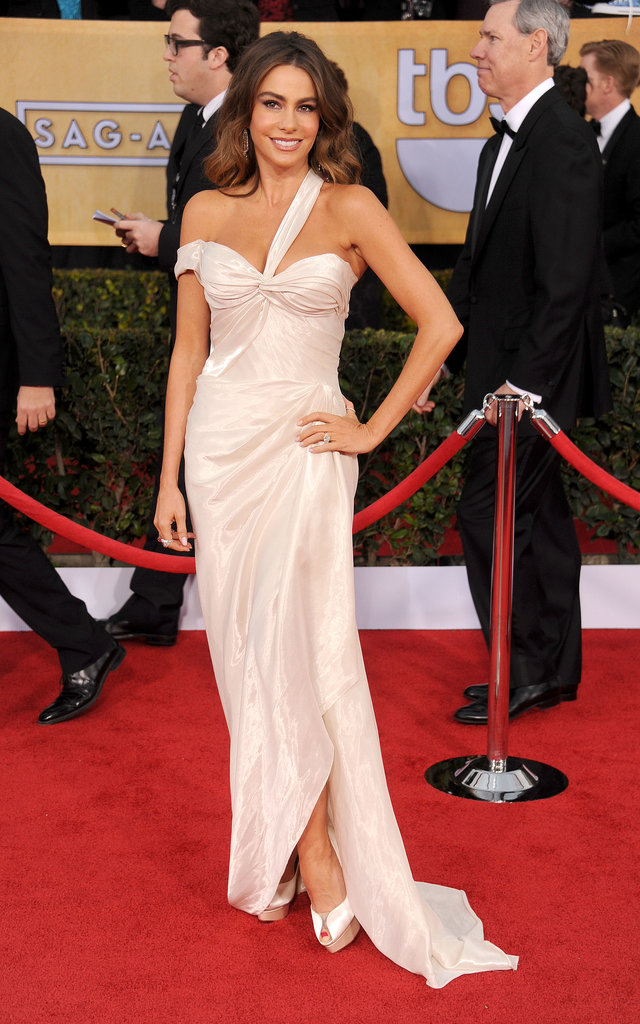 Sofia Vergara struck her famous pose in a pearly white Donna Karan Atelier draped confection at the 2013 SAG Awards. She accessorized her bombshell look with peep-toe Charlotte Olympia pumps and sparkling diamond jewels from Neil Lane.