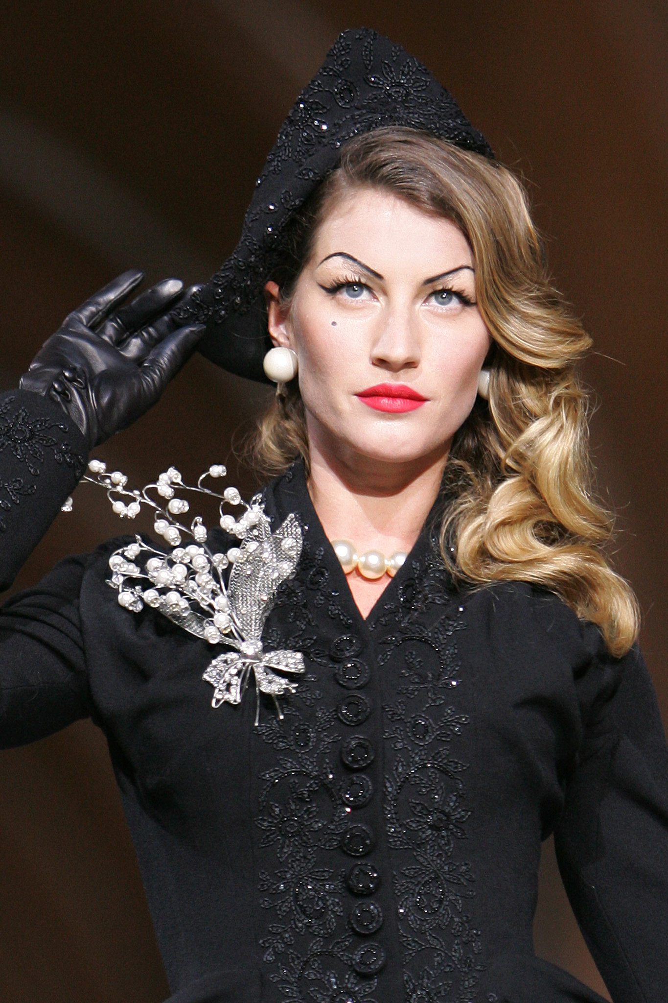 With arched brows, red lips, and a penciled-in beauty mark, Gisele commanded the runway at Dior's 60th anniversary show in Paris.