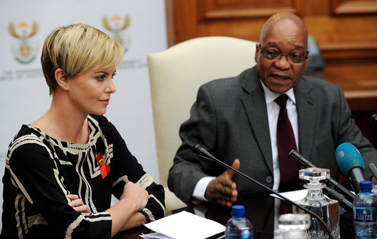 Charlize Theron wore a red ribbon during the press conference as she spoke with South African President Jacob Zuma.