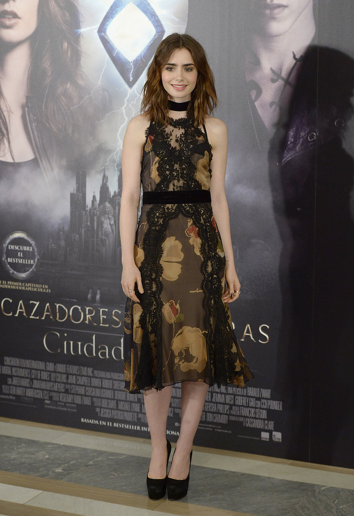 We were surprised to see Lily choose a belly-covering Dolce & Gabbana dress at her photocall in Madrid. The actress opted for an ultrafeminine lace and floral dress that she paired with Brian Atwood platform pumps.