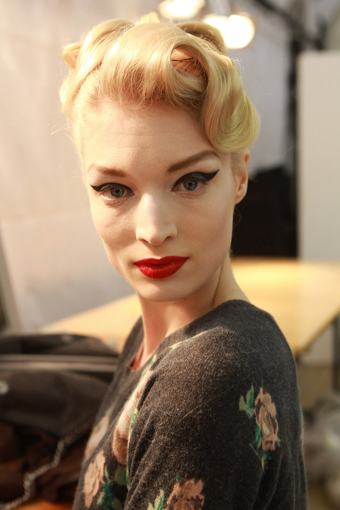 Another Dior show, another dramatic vintage-inspired beauty look! For Haute Couture Spring 2011, elegant updos with artfully placed curls were teamed with the classic combo of flicked liner and red lips.