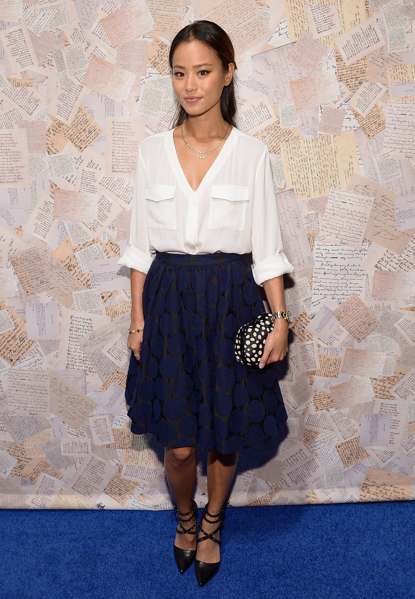 Jamie Chung was soft in a white blouse and a navy flowy skirt at the Alice + Olivia presentation. She added edge via a dotted clutch and studded strappy pumps, both by Alice + Olivia.