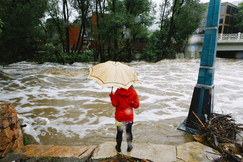 A woman watched as Boulder Creek rushed past her following a flash flood.