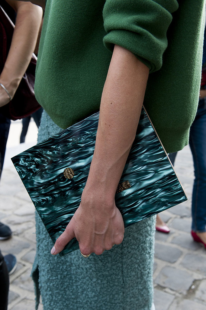 Perfect accessory placement: a moody clutch echoes the same hues in her skirt.