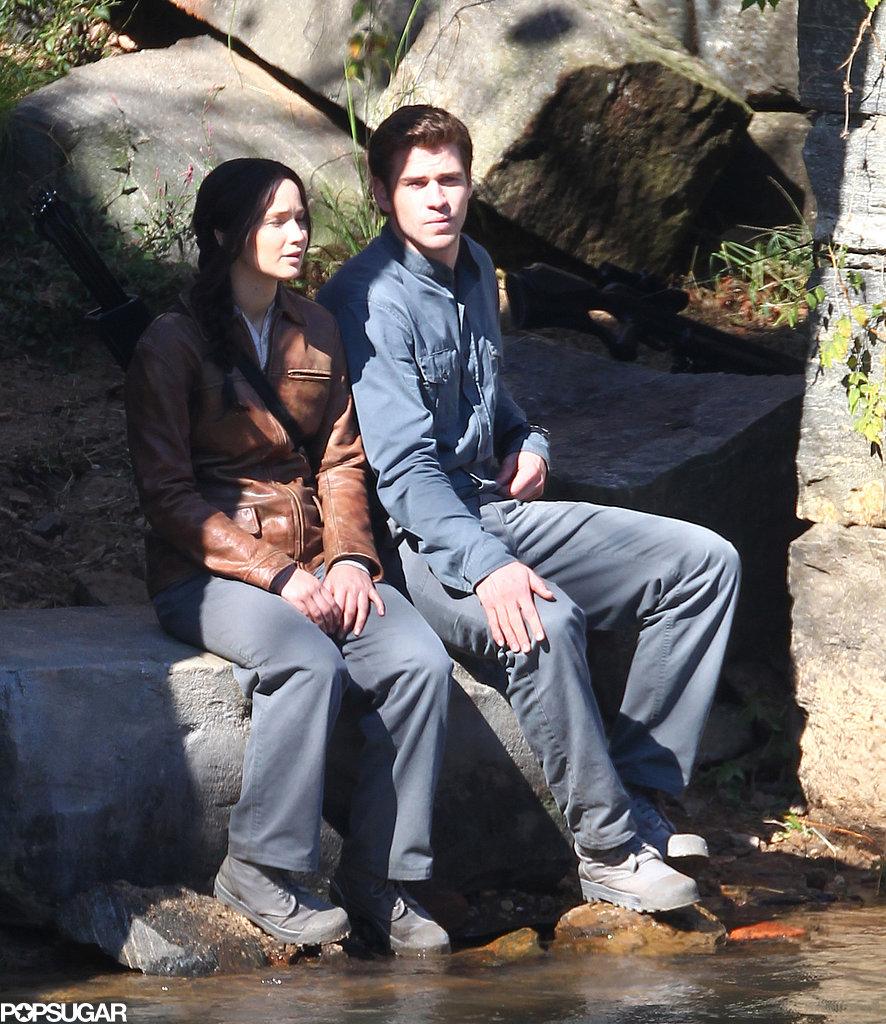 Jennifer Lawrence sat on a rock beside Liam Hemsworth.