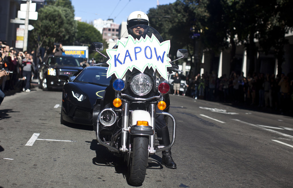 """A police officer escorted the Batmobile with a """"kapow"""" sign on the front of his motorcycle."""