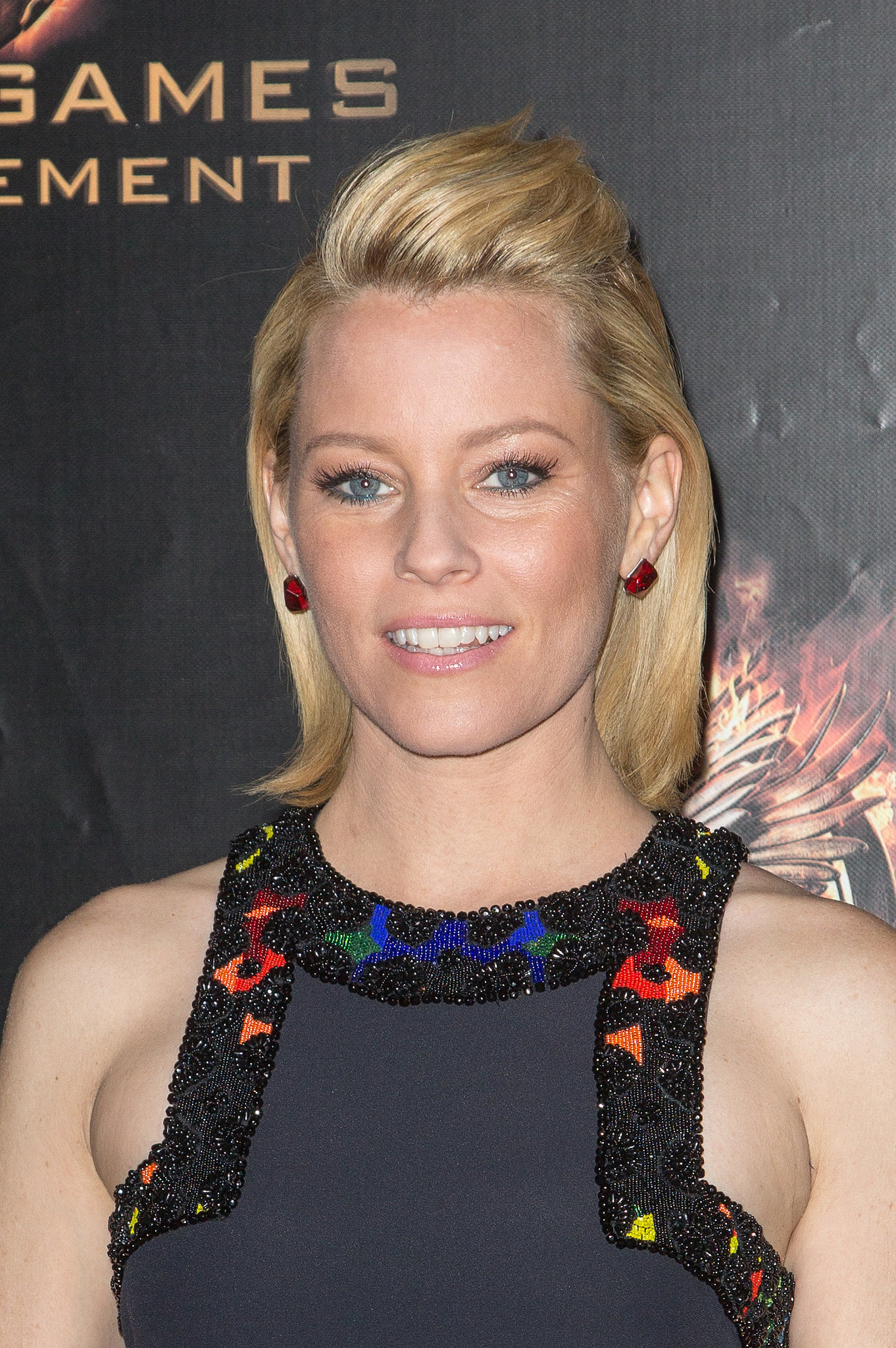 At the Paris premiere of Catching Fire, Elizabeth Banks wore a half-up hairstyle and barely there makeup.