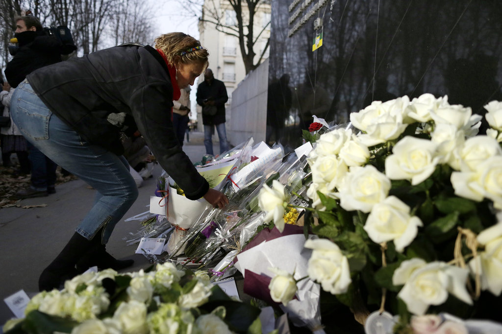 A woman set flowers on the ground of the South African Embassy in Paris.