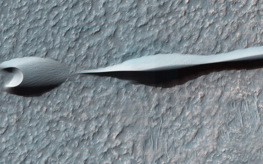 """Sand dunes like these seen in this image have been observed to creep slowly across the surface of Mars through the action of the wind. These are a particular type of dune called a 'barchan,' which forms when the wind blows in one direction (here, east to west) for long periods of time. Barchan dunes are common on Mars and in the desert regions of the Earth."" Source: NASA/JPL/University of Arizona"