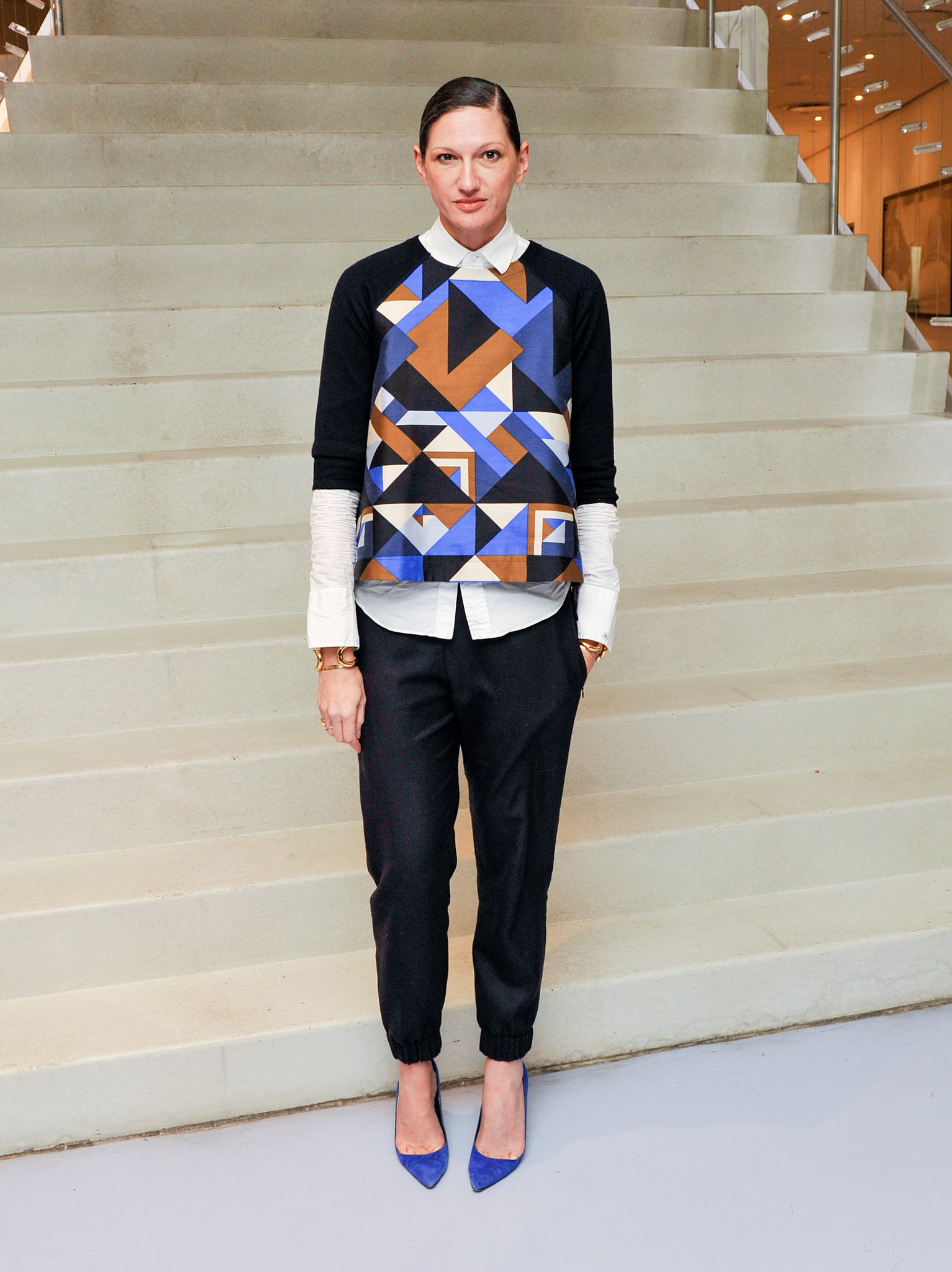 We love that she routinely skips the cocktail dress in favor of an outfit like this combo of black slacks, cobalt pumps, and a geometric print top worn over a button-up shirt.