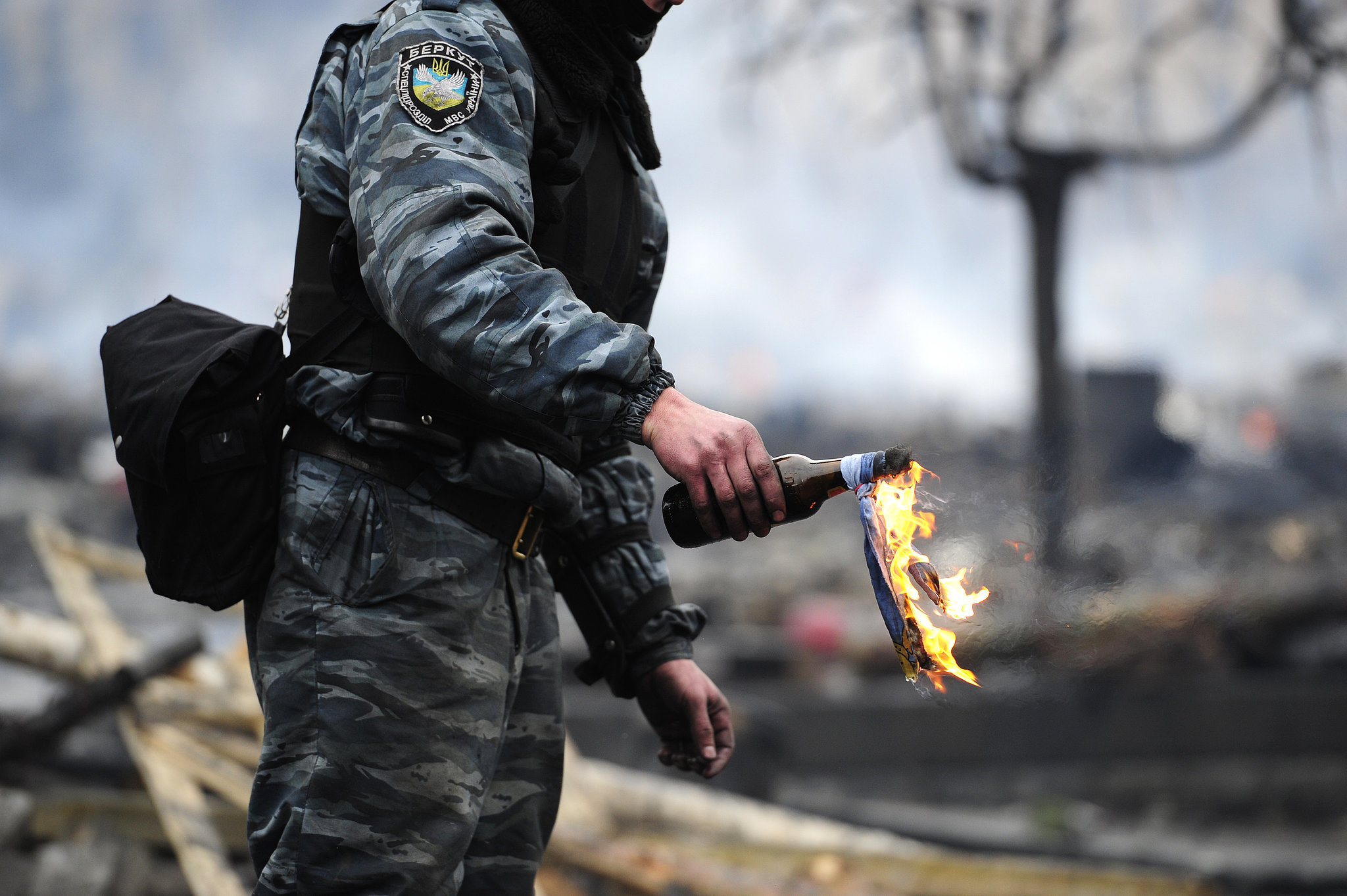A man prepared to throw a flaming bottle.