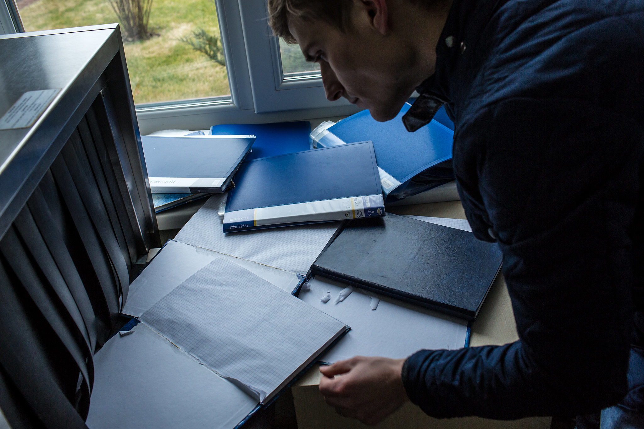 A man looked through record books in one of the security booths on the estate.