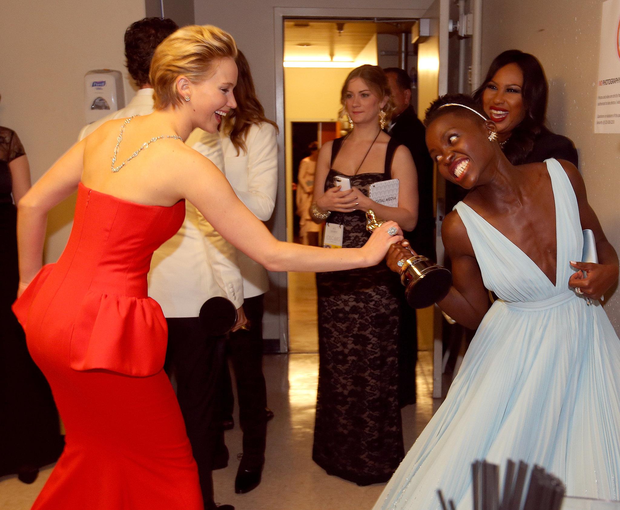 Jennifer Lawrence playfully grabbed Lupita's Oscar.
