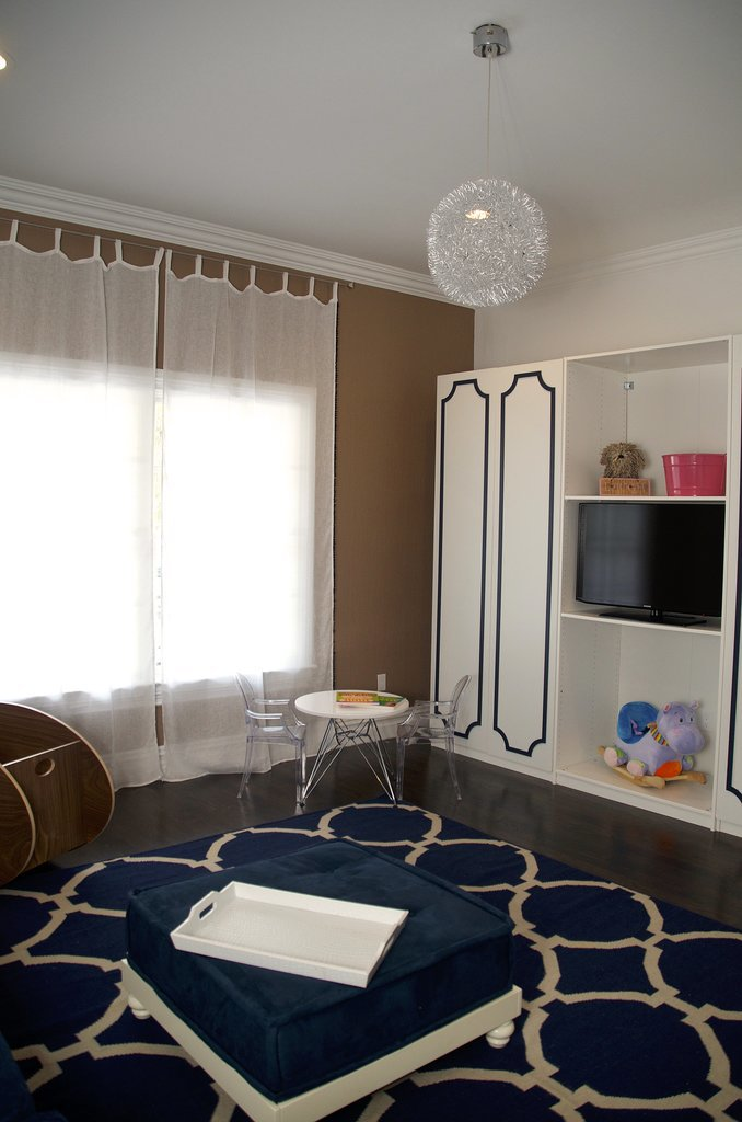 More of Vanessa's picks and resources: The pom-poms on the New Arrivals drapes are so sweet, but the linen is transparent to ensure lots of light gets into Alena's play space. I can't forget [to mention] the fact that the entire navy wall is chalkboard! I told them not to disclose this to Alena too early, but once she can distinguish which walls are OK to draw on, they can tell her. All of the paint is Lullaby Paints, which has no VOCS. The modern and funky light fixture and kids' table and chairs are by Zuo Modern. What's more fun than pint-sized ghost chairs? Source: Vanessa Antonelli for Nessa Lee Baby