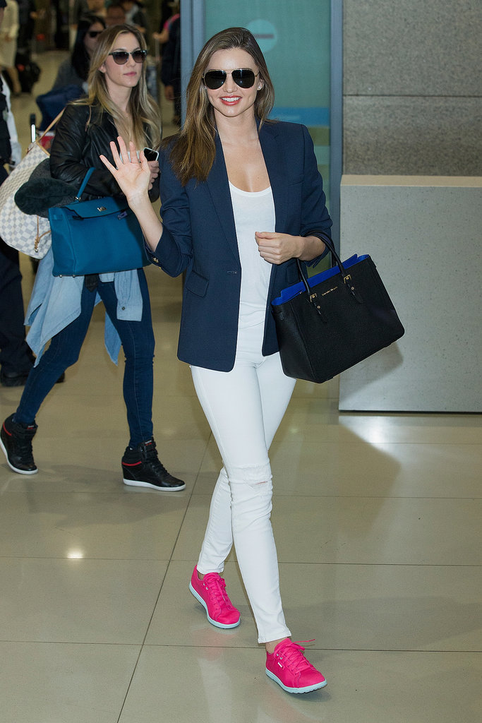 Miranda Kerr waved to fans after touching down at the airport in South Korea.