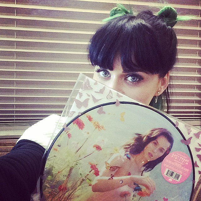 Katy Perry snapped a pic with a copy of her vinyl record on Saturday and, in the process, showed off her green-and-black hair.  Source: Instagram user katyperry