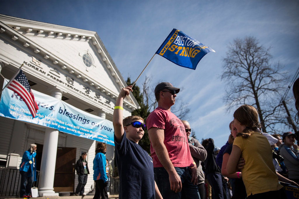 "An 8-year-old boy waved a ""Boston strong"" flag."