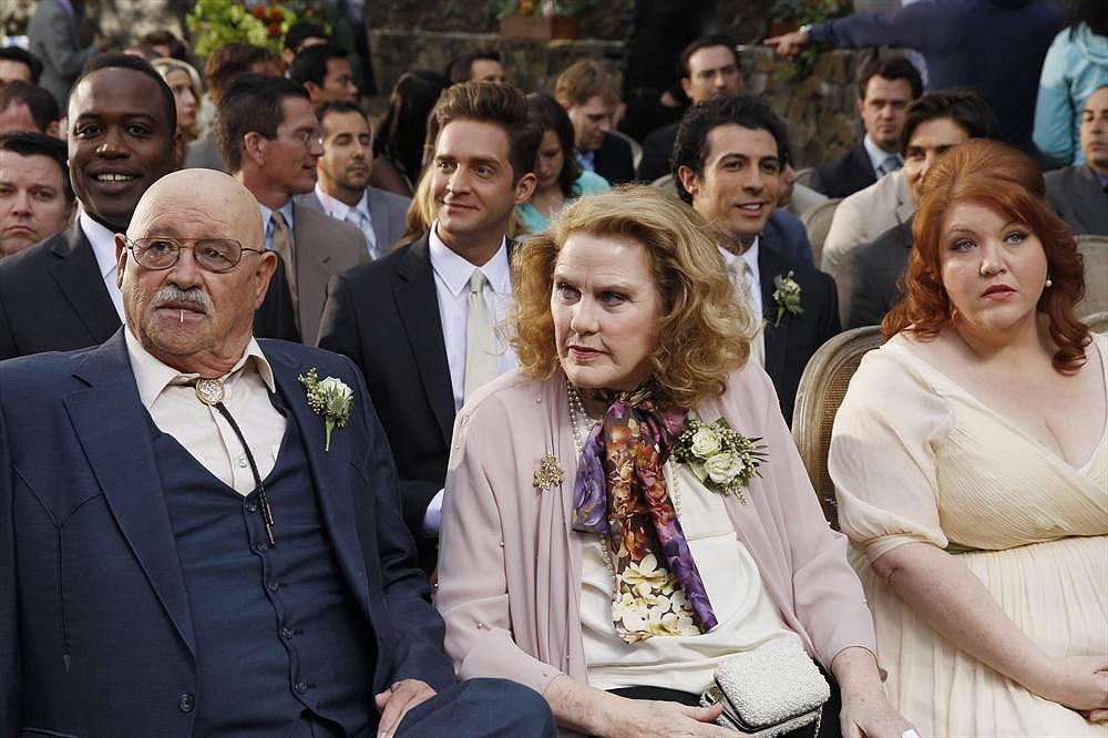 Merle (Barry Corbin), Barb (Celia Weston), and Pam (Dana Powell) sit in the audience.