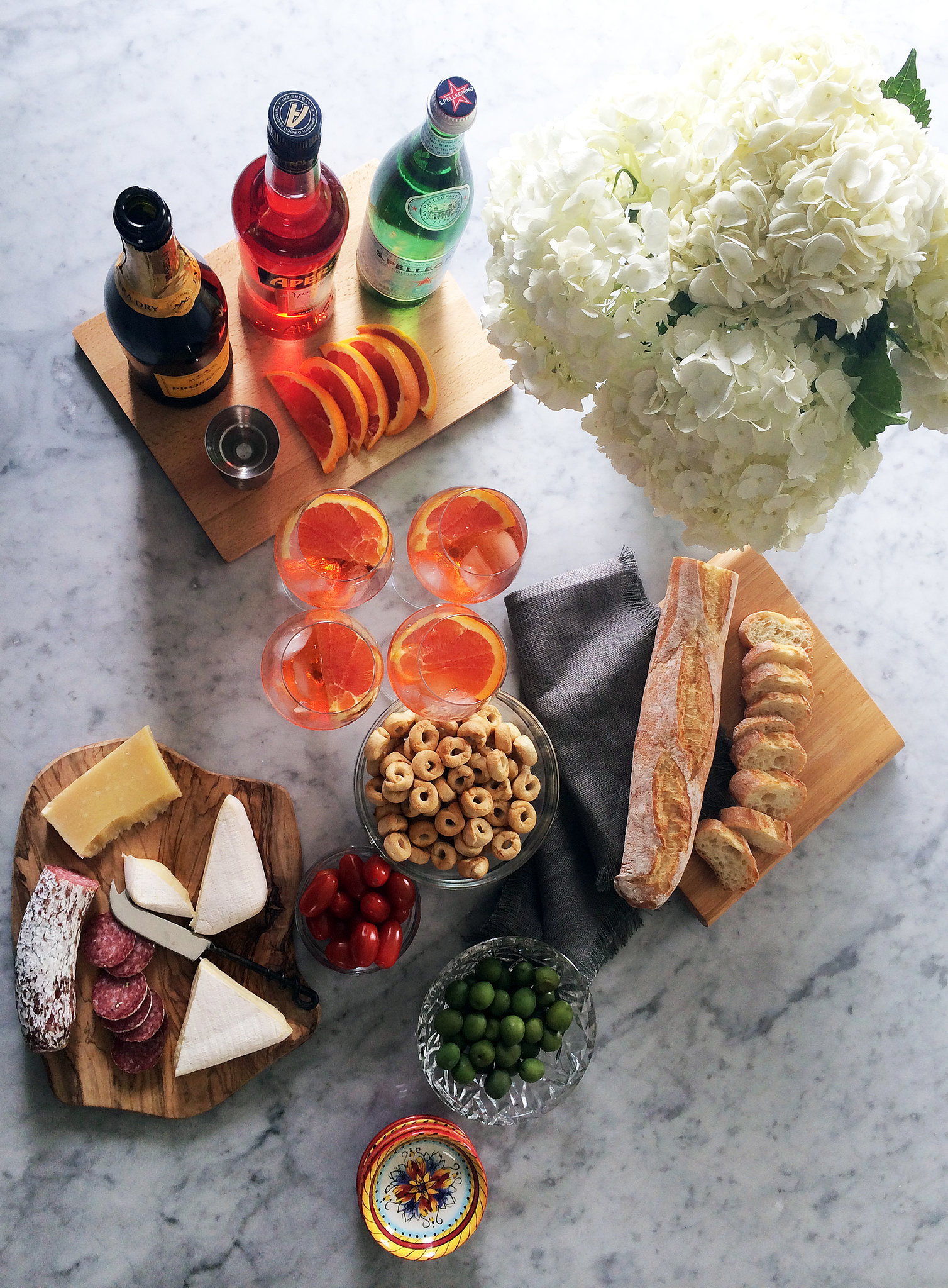 Aperol Spritz isn't too well known in the US, which is what makes it special to serve and such a conversation starter. Her other entertaining essentials: fresh flowers, cheese, Champagne, and an after-dinner drink, be it cognac or whiskey.
