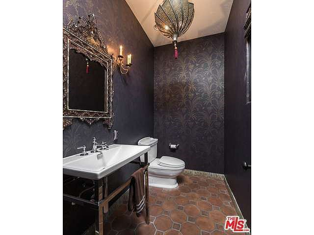 Moody wallpaper sets the tone in this bathroom. Source: Coldwell Banker