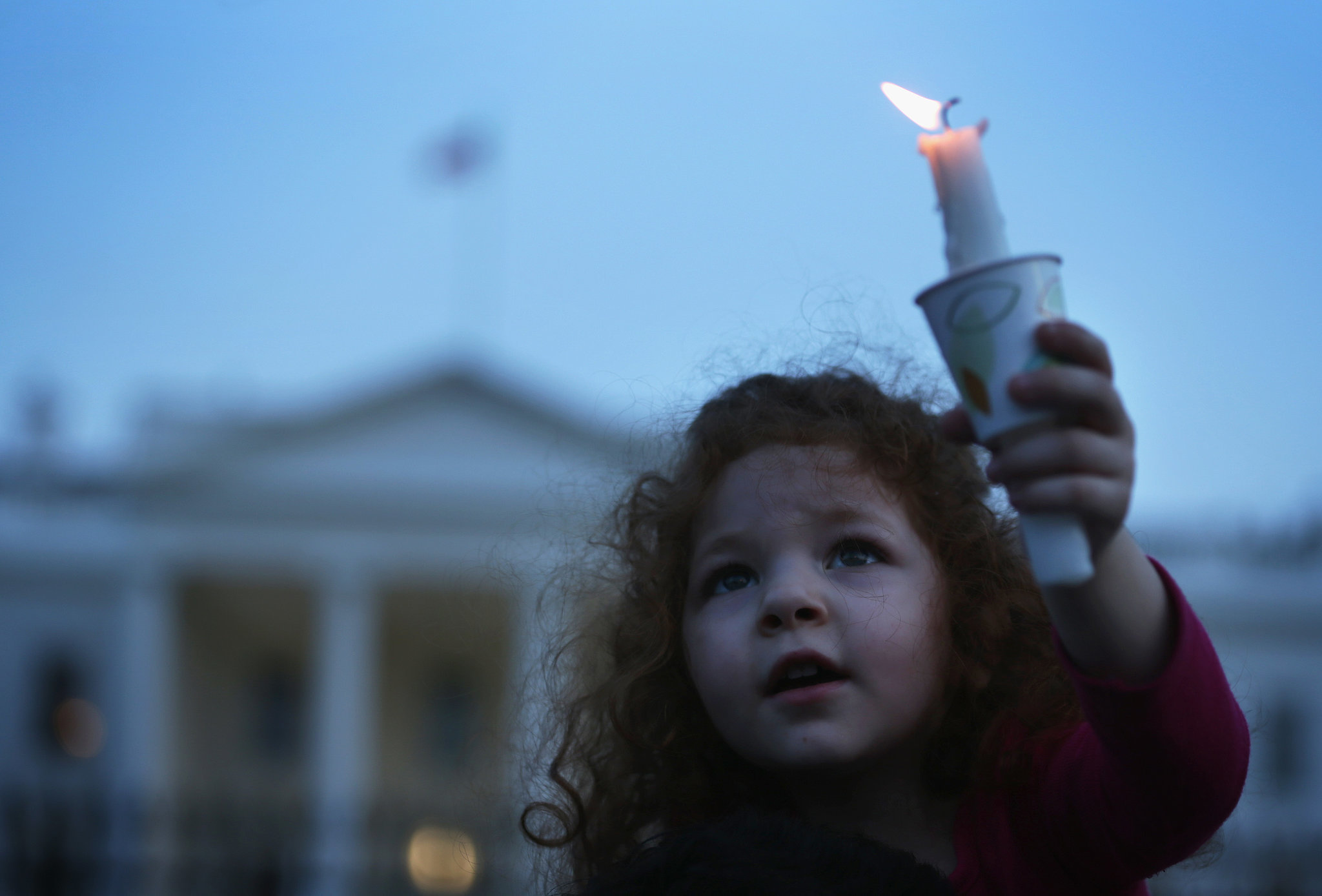 little girl held up a candle during a vigil in front of the White ...