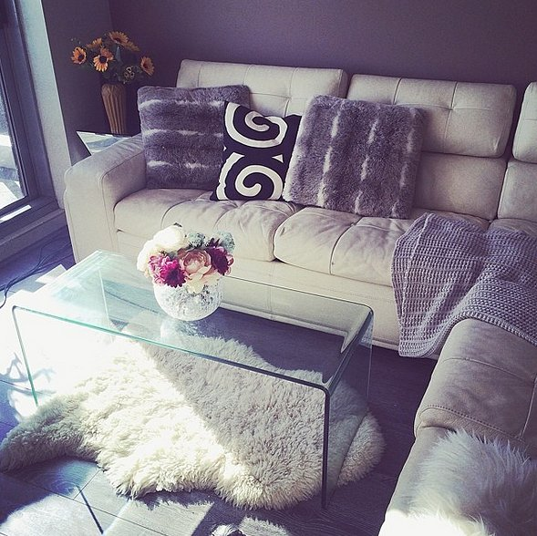 Play up your chic style by using contrasting elements in your living space. A slick glass coffee table looks great paired with a lush sheepskin rug and soft pillows.  Source: Instagram user elaineji88
