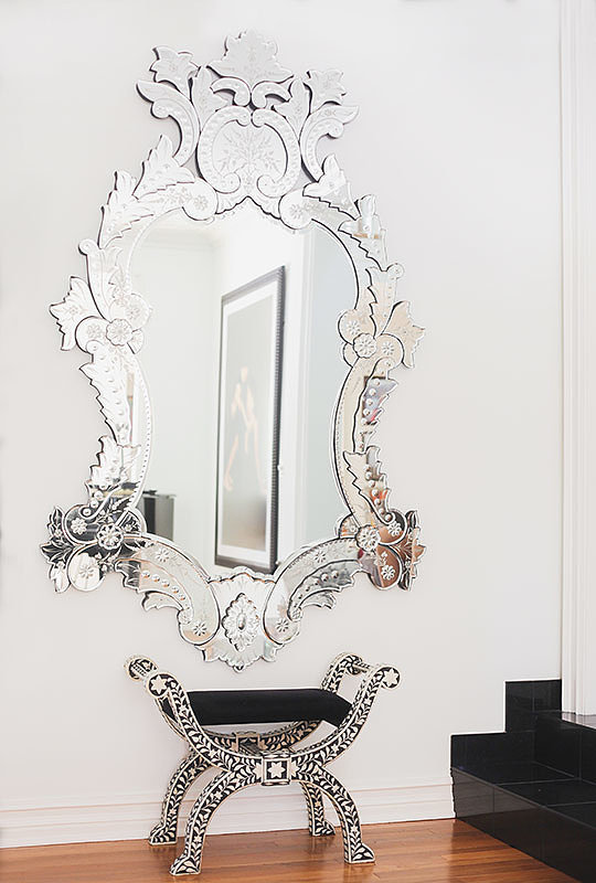 A well-placed mirror will open up a small room and will help give purpose to awkward blank walls. Photo by Tessa Neustadt. via Homepolish