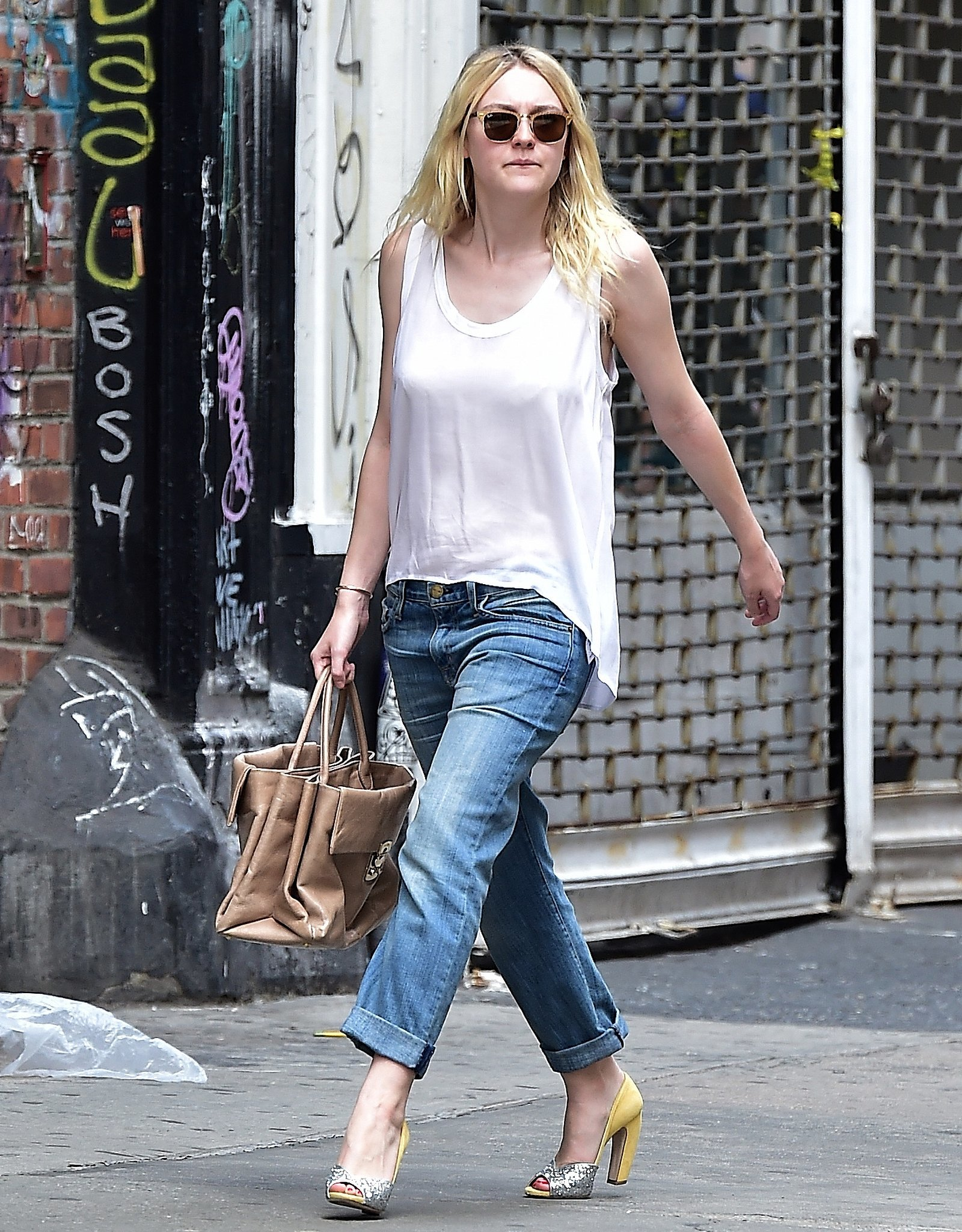 Dakota opted for a pair of slouchy Current/Elliott The Fling jeans, which she double cuffed, and a white, loose-fitting high-low top. Her accessories included a tan leather top-handle bag and matching sunglasses, and whereas we might cap off such a comfortable look with ballerina flats or smoking slippers, the stylish star elevated her ensemble with glittery, two-toned peep-toe heels. We love how she took an otherwise supercasual day look and gave it some seriously unexpected sparkle.