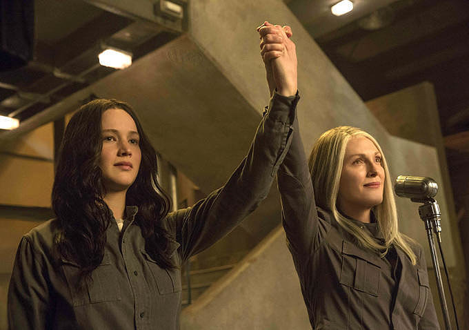Katniss and President Coin raise their hands in union. And they almost look like they're smiling.