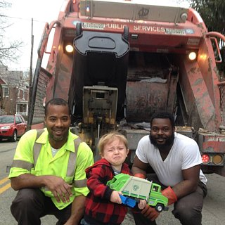 Little Boy Takes Photo With Garbagemen