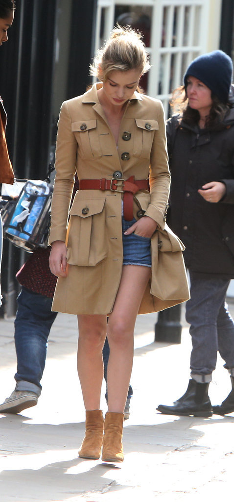 Georgia May Jagger belted her trench for a fitted style and revealed casual denim shorts underneath.