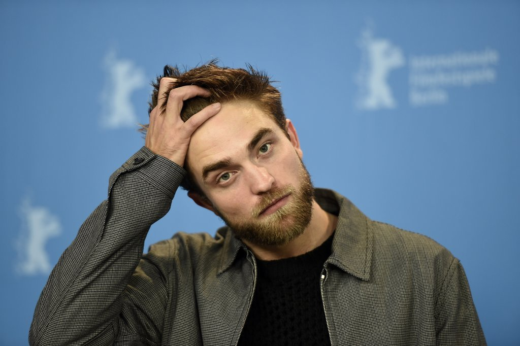 Rob was serious while stroking his hair during the Berlin Film Festival in February 2015.