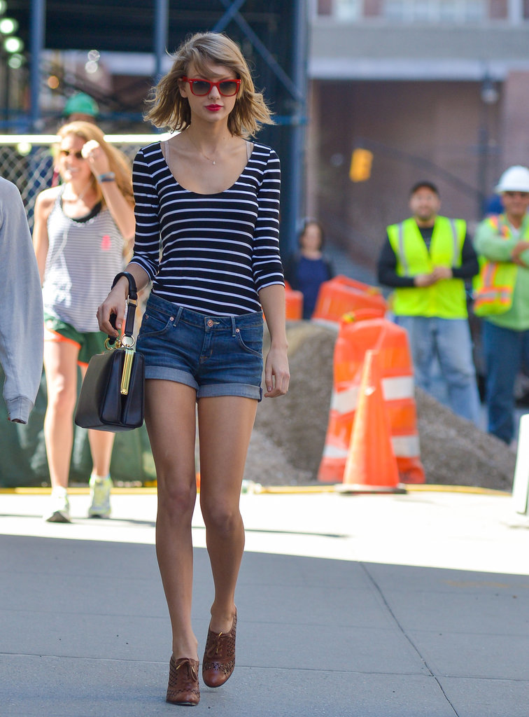 Taylor Swift revamped a pair of denim shorts with a ladylike handbag, classic tee, and walkable booties.