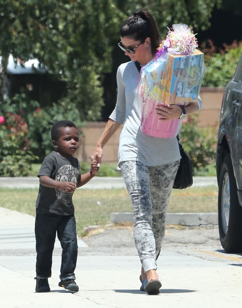 Sandra Bullock held her son Louis's hand on the way to a birthday party in LA.